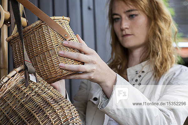 Young woman looking at wickerwork basket in shop