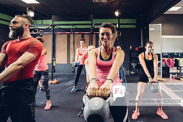 Frauen trainieren in Turnhalle mit männlichem Trainer und heben Kesselglocken
