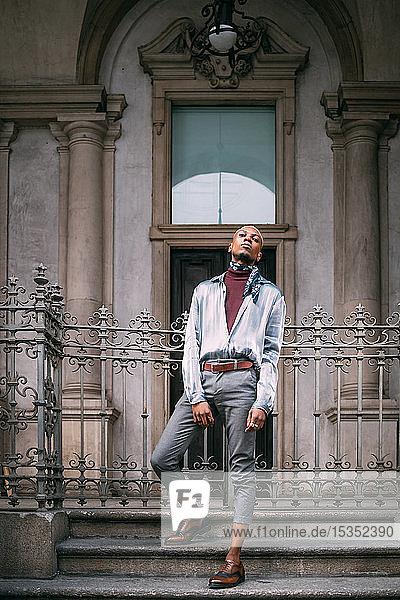 Stilvoller Mann steht auf Stufen eines historischen Gebäudes  Mailand  Italien