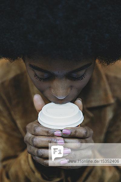 Junge Frau mit Afro-Haaren nippt an heißem Getränk