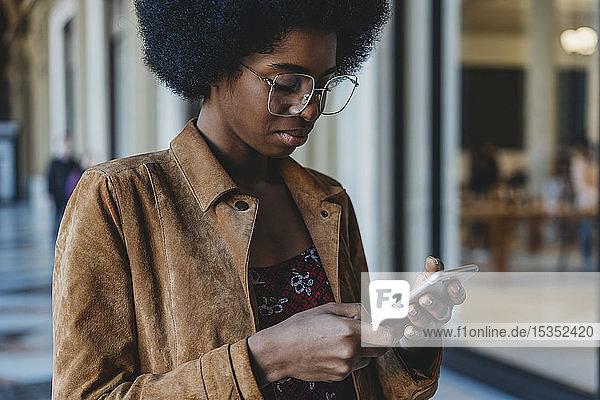 Junge Frau mit Afro-Haaren benutzt Smartphone im Gebäudekorridor