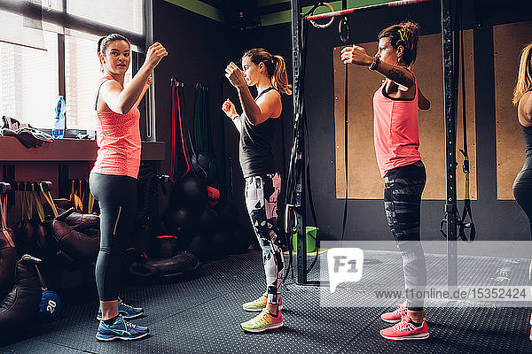 Women training in gym  with arms raised  side view