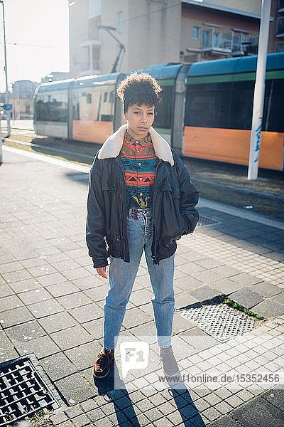 Kühle junge Frau auf dem sonnenbeschienenen städtischen Bürgersteig  Porträt