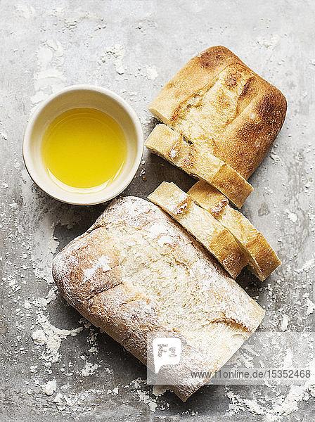 Stilleben eines bemehlten und unbemehlten Ciabattabrötchens auf Backblech mit Schüssel Olivenöl  Draufsicht