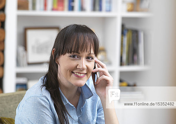 Woman relaxing and catching up with friends over the phone in her lounge