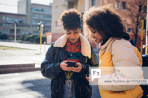 Two cool young women looking at smartphone on urban sidewalk