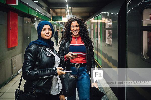 Junge Frau im Hidschab mit Freundin in der U-Bahn-Station  Porträt