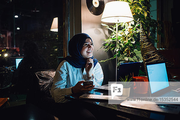 Young woman in hijab at a cafe table laughing