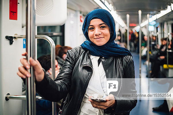 Young woman in hijab with smartphone on subway train  portrait