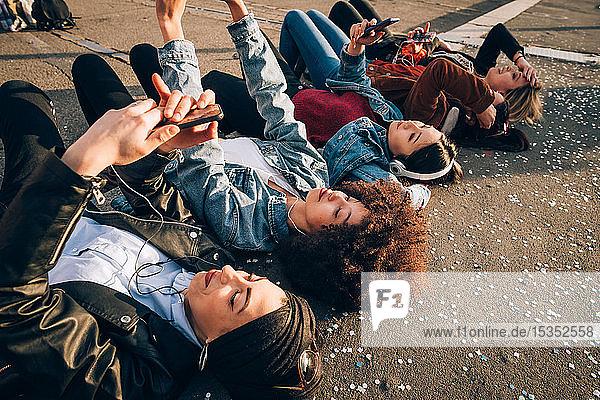 Freunde auf der Bordsteinkante gemeinsam Selbsthilfe und Smartphones nutzen  Mailand  Italien