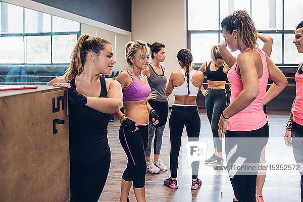 Gruppe von Frauen trainiert im Fitnessstudio  macht eine Pause und plaudert