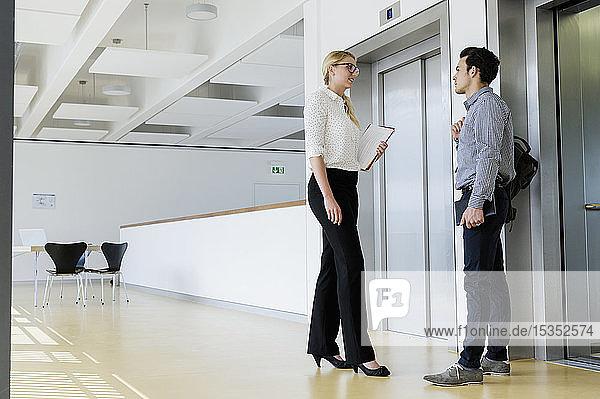 Kollegen im Gespräch beim Aufzug