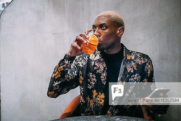 Ein stilvoller Mann genießt sein Getränk mit dem Handy in der Hand