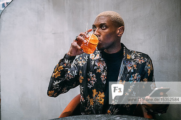 Stylish man enjoying drink  cellphone in hand