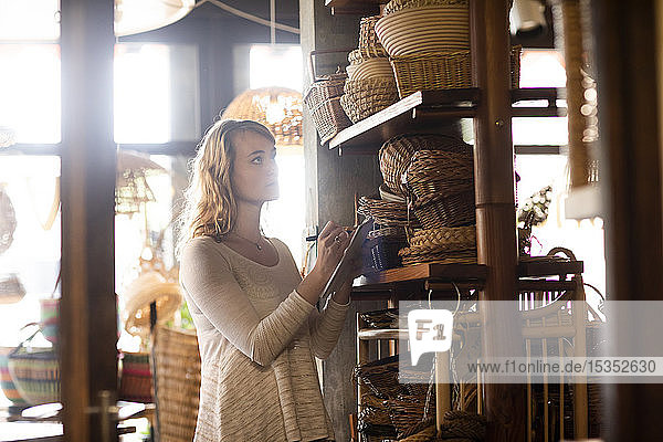 Young female basket maker stock taking in shop