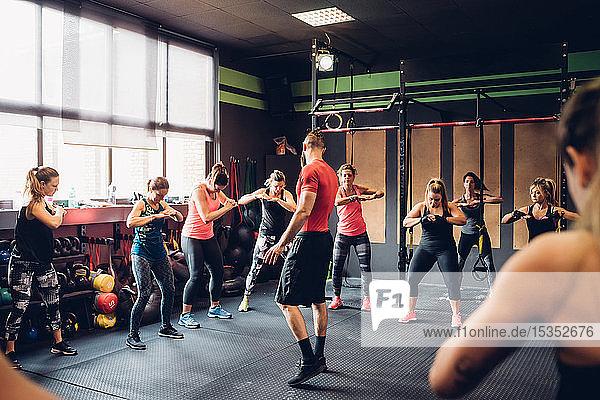 Gruppe von Frauen  die mit einem männlichen Trainer im Fitnessstudio trainieren  mit den Händen zusammen