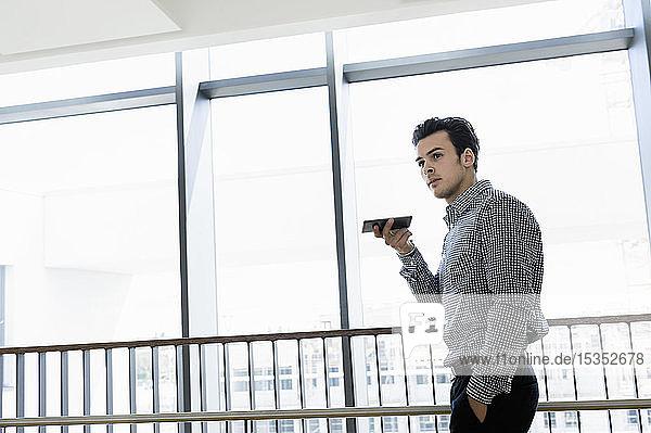 Geschäftsmann benutzt Smartphone im Bürokorridor