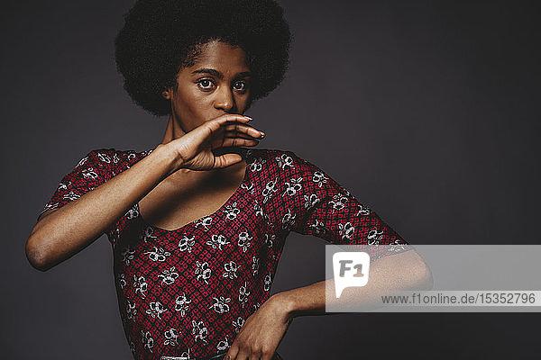 Junge Frau mit afrofarbenen Haaren  die den Mund bedecken  grauer Hintergrund