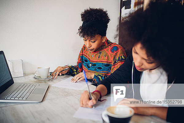 Zwei junge Frauen schreiben Notizen am Café-Tisch