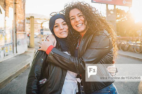 Junge Frau im Hidschab und beste Freundin umarmen sich in der Stadt  Porträt
