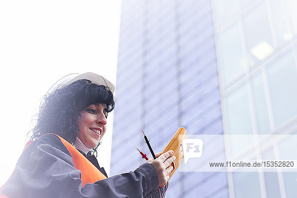 Female surveyor looking at distance meter outside office building