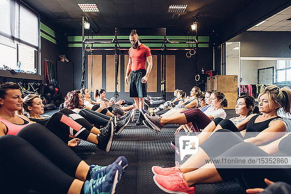 Große Gruppe von Frauen trainiert in Turnhalle mit einem männlichen Trainer  der mit angehobenen Beinen auf dem Boden sitzt