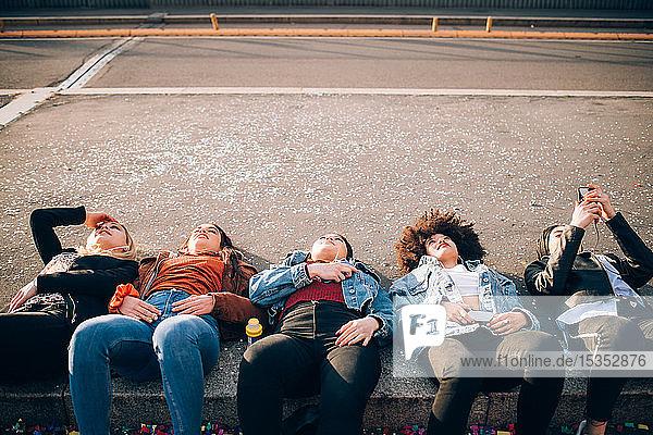 Friends lying on kerb  Milan  Italy