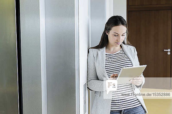 Geschäftsfrau benutzt digitales Tablett neben dem Aufzug