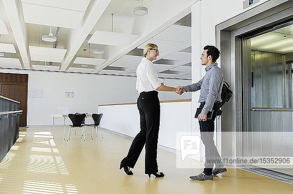 Kollegen schütteln sich die Hand und unterhalten sich in der Nähe des Aufzugs