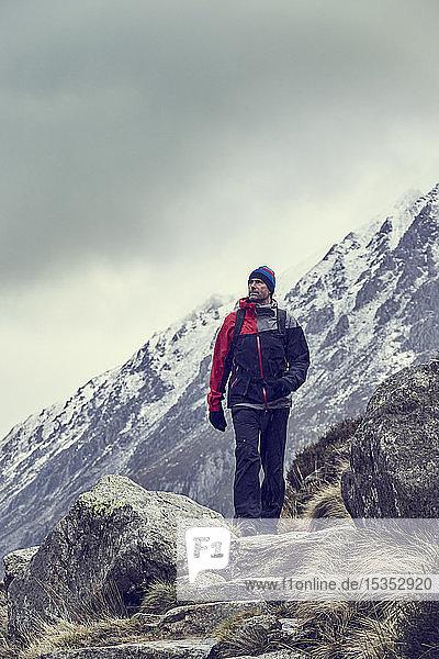 Männlicher Wanderer wandert in zerklüfteter Landschaft mit schneebedeckten Bergen  Llanberis  Gwynedd  Wales