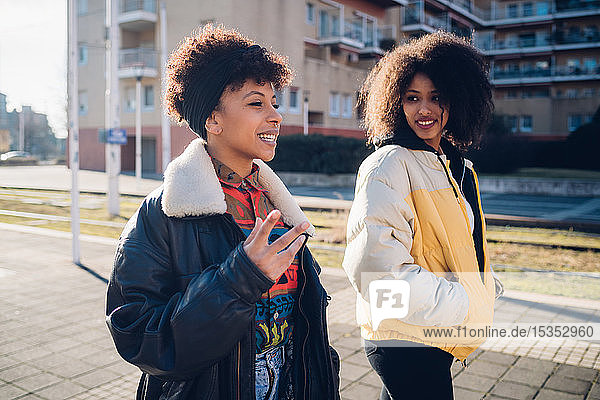 Two young women walking and talking on urban sidewalk