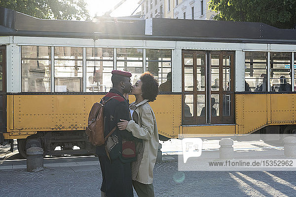 Paar küsst sich auf der Straße  Straßenbahn fährt im Hintergrund vorbei  Mailand  Italien