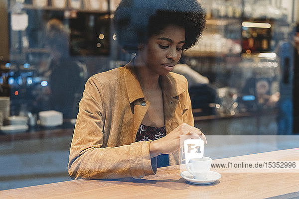 Junge Frau mit Afro-Haaren beim Kaffeetrinken im Café