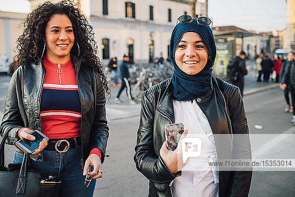 Junge Frau im Hidschab mit bestem Freund auf der Straße der Stadt