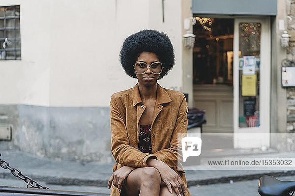 Junge Frau mit Afro-Haaren wartet vor dem Geschäft