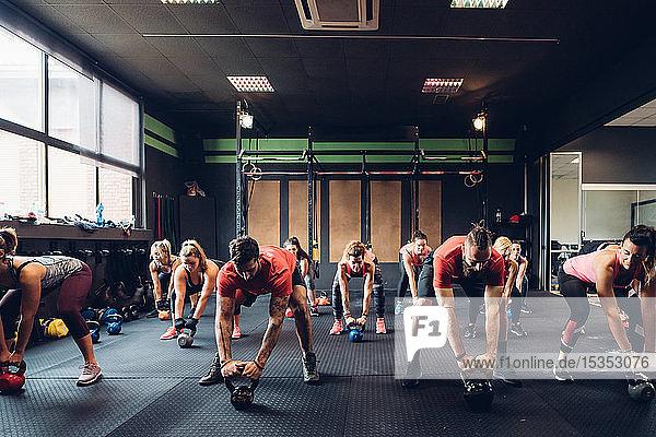 Frauen trainieren in Turnhalle mit männlichen Trainern und bereiten sich auf das Heben von Kesselglocken vor