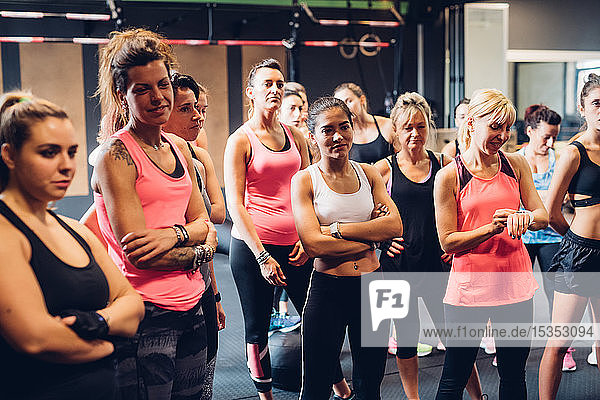 Group of women training in gym  listening