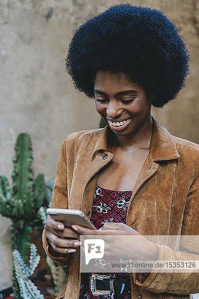 Junge Frau mit Afro-Haaren benutzt Smartphone in der Stadt