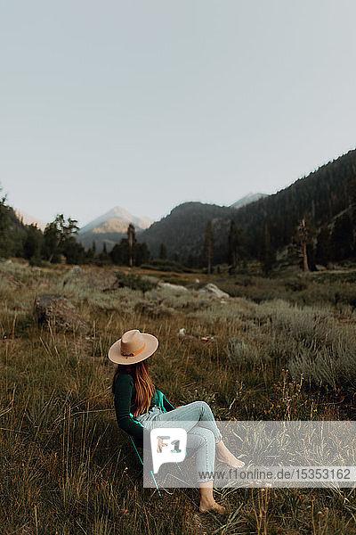 Junge Frau in Stetson entspannt auf Liegestuhl im ländlichen Tal  Mineral King  Kalifornien  USA