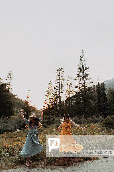 Two women in maxi dresses dancing in rural valley  Mineral King  California  USA