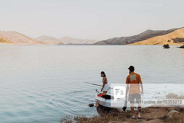 Couple carrying kayak to lake  Kaweah  California  United States