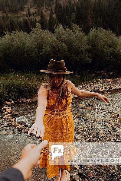 Schwangere Frau in orangefarbenem Maxikleid  die aus ländlichem Fluss nach der Hand greift  Mineral King  Kalifornien  USA
