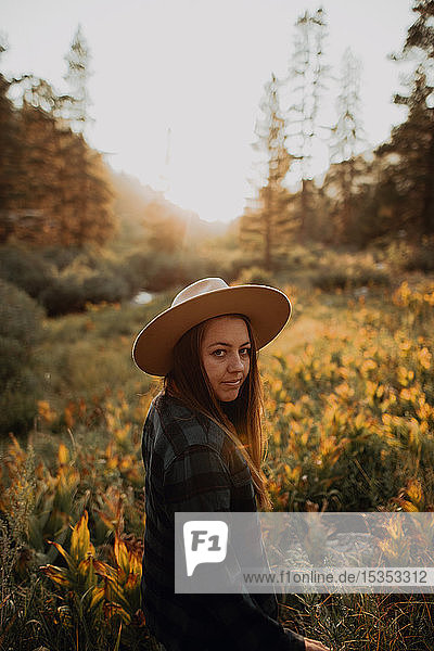 Young woman in stetson looking back in rural valley at sunset  Mineral King  California  USA