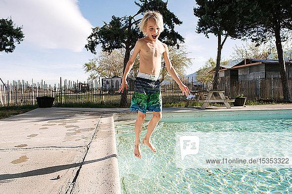 Boy jumping into swimming pool  Olancha  California  US