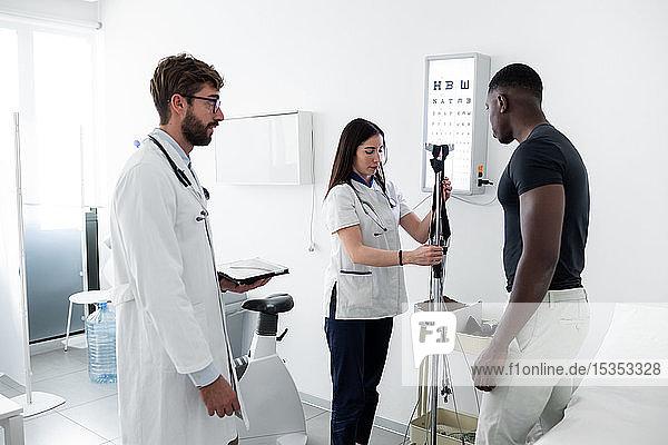Arzt beobachtet Krankenschwester bei der Untersuchung des Patienten im Sprechzimmer