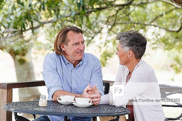 Couple enjoying coffee under shade in garden