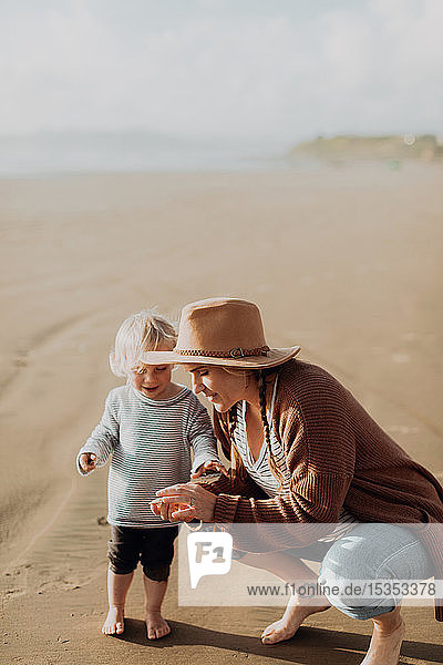 Mother and toddler playing on beach