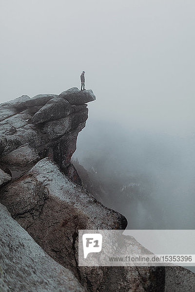 Wanderer genießt Aussicht auf nebeldurchzogenes Tal  Yosemite National Park  Kalifornien  Vereinigte Staaten