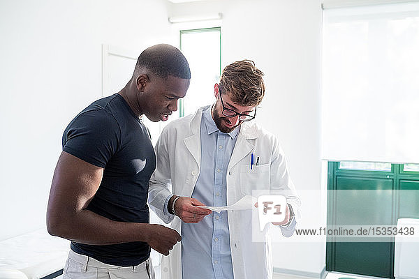 Doctor and patient reading medical results in hospital