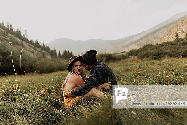 Mid adult couple sitting down hugging in rural valley  portrait  Mineral King  California  USA